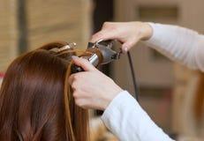 El peluquero hace a la muchacha del peinado con el pelo rojo largo en un salón de belleza fotos de archivo