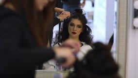 El peluquero hace los hairdress a la muchacha hermosa en un salón de belleza almacen de video