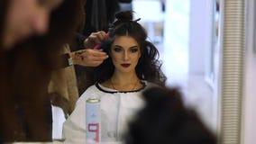 El peluquero hace los hairdress a la muchacha hermosa en un salón de belleza metrajes