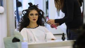 El peluquero hace los hairdress a la muchacha hermosa en un salón de belleza almacen de metraje de vídeo