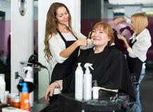 El peluquero hace para cortar para la mujer imagen de archivo