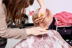 El peluquero hace el peinado elegante para una mujer mayor foto de archivo