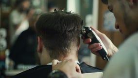El peluquero hace peinado a un hombre con una barba almacen de video