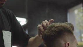 El peluquero hace el pelo que diseña con la laca para el pelo después de corte de pelo en la peluquería de caballeros Hombre cauc almacen de metraje de vídeo