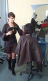 El peluquero hace pelo-se viste al brunette joven fotos de archivo libres de regalías