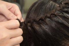 El peluquero hace trenzas Imágenes de archivo libres de regalías