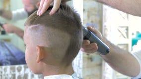 El peluquero hace un corte de pelo para el niño pequeño con el hairclipper en salón de belleza almacen de video