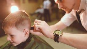 El peluquero hace un corte de pelo para un pequeño bebé divertido almacen de metraje de vídeo