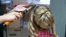 El peluquero hace un peinado de moda en un pelo rubio largo almacen de video