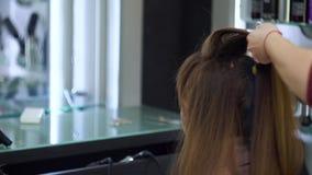 El peluquero hace un peinado festivo de moda en el pelo largo metrajes