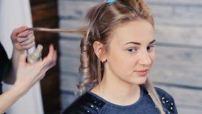 El peluquero hace un peinado para una muchacha metrajes