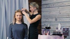 El peluquero hace un peinado para una muchacha almacen de video