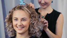 El peluquero hace un peinado para una muchacha almacen de metraje de vídeo