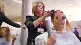 El peluquero hace un peinado y diseñar de moda Peluquero de sexo femenino que se seca el pelo masculino del ` s del cliente en sa almacen de metraje de vídeo