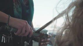 El peluquero hace una colocación magnífica de una mujer rubia metrajes