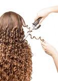 El peluquero hace usando la mujer del pelo rizado del fórceps aislada en blanco Fotografía de archivo