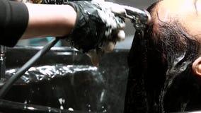 El peluquero lava el pelo del cliente en peluquería de caballeros almacen de metraje de vídeo