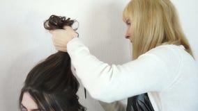 El peluquero levantó el pelo en el modelo principal almacen de metraje de vídeo
