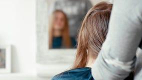 El peluquero peina con el cepillo para el pelo el pelo del cliente Reflexión borrosa en espejo almacen de video