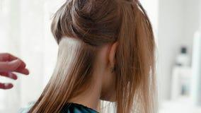 El peluquero peina con el cepillo para el pelo el pelo recto mojado femenino en salón de belleza almacen de video