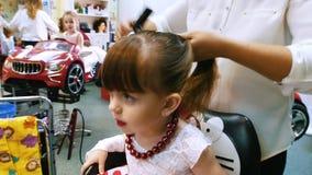 El peluquero peina el pelo con una crema batida de pelo para una muchacha linda Tiro del primer almacen de video