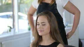 El peluquero, peluquero prepara a la muchacha adolescente en blanco compone el sitio para la peluquería metrajes