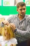 El peluquero principal de moda hace que un updo elegante el pelo rubio joven de la mujer muestra Imagen de archivo