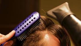 El peluquero profesional irreconocible el cabello seco de su cliente masculino, primer metrajes