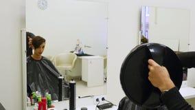 El peluquero profesional muestra la vista trasera del corte de pelo usando el espejo al cliente femenino satisfecho hermoso en a almacen de video