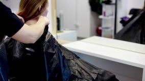 El peluquero puso el peinoir en el salón de la peluquería almacen de video