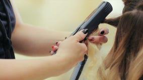 El peluquero que hace el peinado en salón de belleza Mujer joven en un salón de belleza metrajes