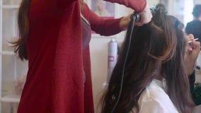 El peluquero que hace pelo-hace mientras que componga al artista que aplica el cosmético metrajes