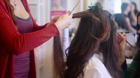 El peluquero que hace pelo-hace mientras que componga al artista que aplica los sombreadores de ojos almacen de metraje de vídeo