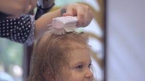 El peluquero seca el secador de pelo una niña Cuidado del cabello en el sal?n de belleza almacen de video