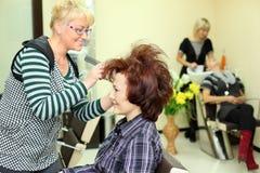 El peluquero sonriente hace el pelo que labra para la mujer Fotografía de archivo