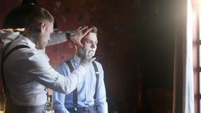 El peluquero tatuado afeita a su cliente tatuado con la maquinilla de afeitar recta, peluquería de caballeros en el estilo de la  metrajes