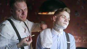El peluquero tatuado afeita a su cliente tatuado con la maquinilla de afeitar recta, peluquer?a de caballeros en el estilo de la  almacen de video