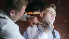 El peluquero tatuado afeita a su cliente tatuado con la maquinilla de afeitar recta, peluquer?a de caballeros en el estilo de la  almacen de metraje de vídeo