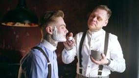 El peluquero tatuado aplica espuma por la brocha de afeitar en la cara de su cliente tatuado, peluquería de caballeros en el esti almacen de metraje de vídeo