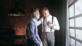 El peluquero tatuado aplica espuma por la brocha de afeitar en la cara de su cliente tatuado, peluquer?a de caballeros en el esti almacen de video