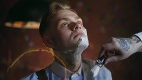 El peluquero tatuado aplica espuma por la brocha de afeitar en la cara de su cliente tatuado, peluquer?a de caballeros en el esti metrajes