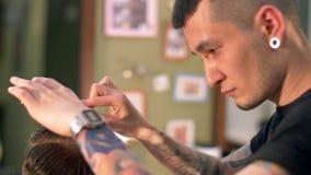 El peluquero tatuado profesional corta al cliente metrajes
