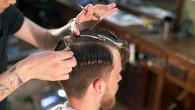 El peluquero tatuado profesional corta al cliente almacen de video