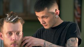El peluquero tatuado profesional corta al cliente almacen de metraje de vídeo