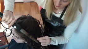 El peluquero trabaja con encresparse del pelo almacen de video