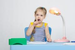 El pensamiento de la muchacha pegó un lápiz en su boca imagen de archivo libre de regalías