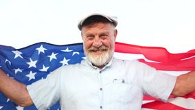 El pensionista americano feliz sostiene la bandera nacional de los E.E.U.U. D?a de la Independencia el 4 de julio almacen de metraje de vídeo