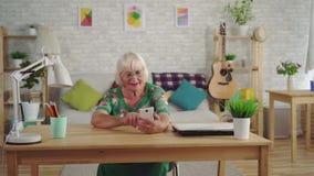El pensionista de la mujer con el pelo gris utiliza un smartphone que se sienta en la tabla en la sala de estar almacen de metraje de vídeo