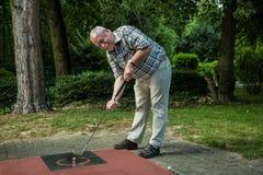 El pensionista en una corte del minigolf se divierte mucho durante su tiro foto de archivo