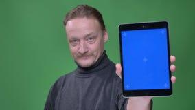 El pensionista rubio en jersey gris muestra la pantalla azul de la tableta para recomendar el app en fondo verde almacen de metraje de vídeo